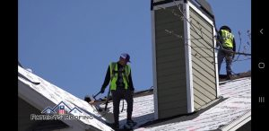 image shows Patriots' Roofing Roofer working on installing a new Roof in Raleigh NC