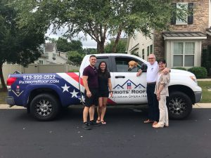 image shows Patriots' Roofing employees standing with happy roofing customer after roof replacement.